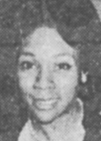 An old B&W photo of a smiling young Black woman with hair coiffed smooth and thick.