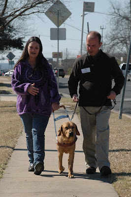 Lifestyles workshop participant working a guide dog with Field Service Manager Marc Gillard