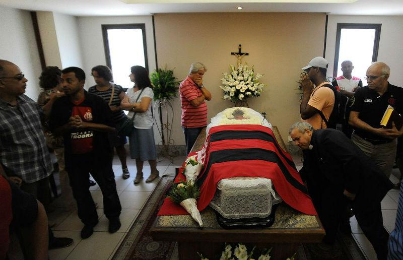 Caixão coberto com a bandeira do Flamengo no centro da foto com. Flores ao fundo. Várias pessoas conversando.