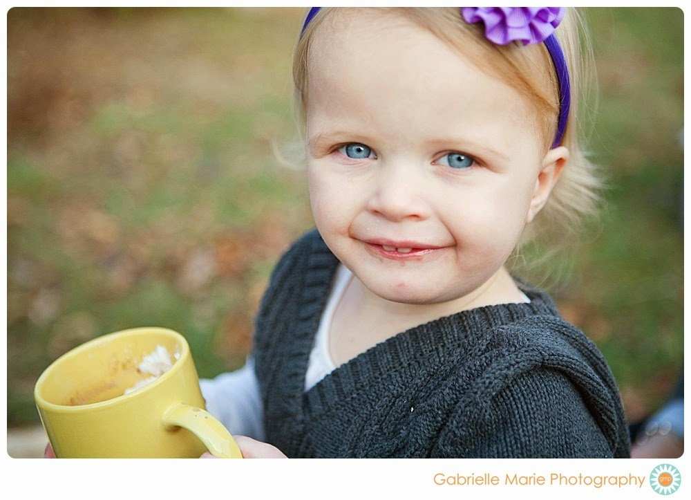 Beautiful little girl with blonde hair and blue eyes drinking hot chocolate
