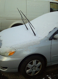windshield wiper blades on a car sticking up with snow covering car
