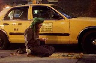 Supir taksi shalat di samping taksinya.