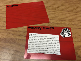 "Two red plastic divider rectangles, one with ""Gloom"" written in the top left, the other with ""Unhappy Homes"" written in the top left and the New Rules and Icon cutout from the box taped on"