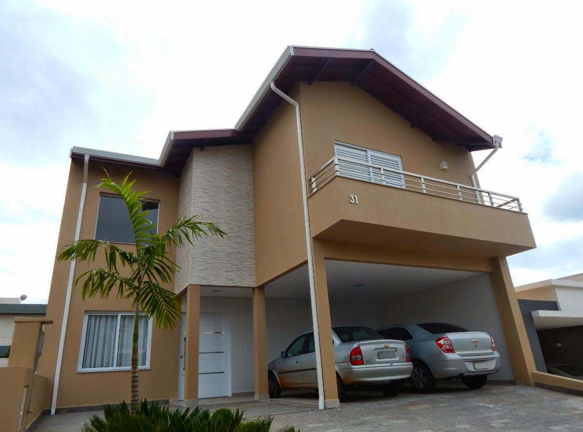 Nesta casa, a porta social pivotante dá acesso a uma grande sala de estar e jantar, com pé-direito duplo.