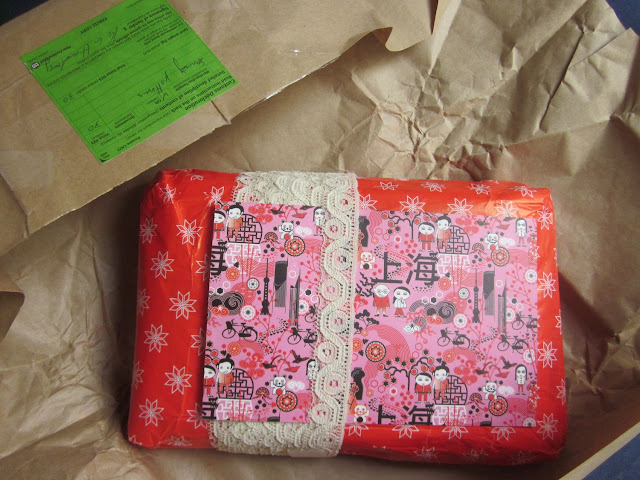Parcel wrapped in lace with a postcard