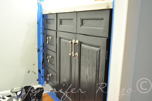 Painting an old bathroom cabinet and adding new handles gives it a whole new look.