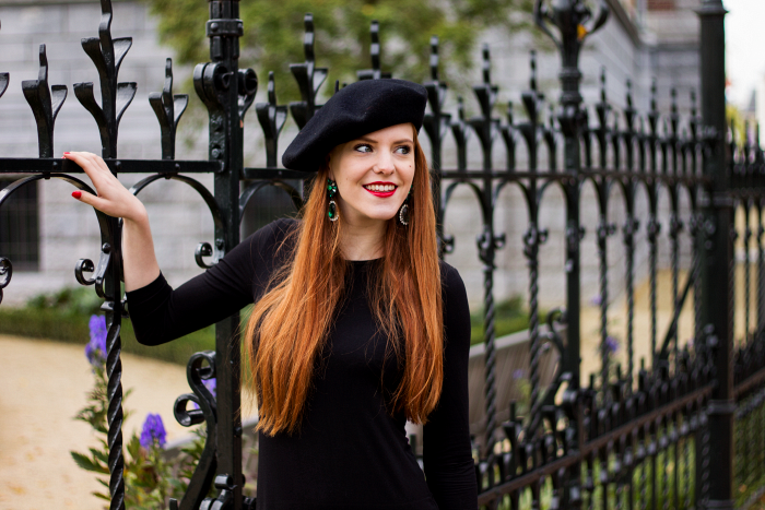 Fashion blogger with red hair, emerald earrings, beret and black dress outfit