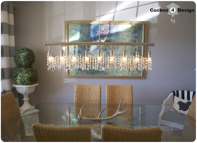 glass dining table with wicker chairs and cellula chandelier