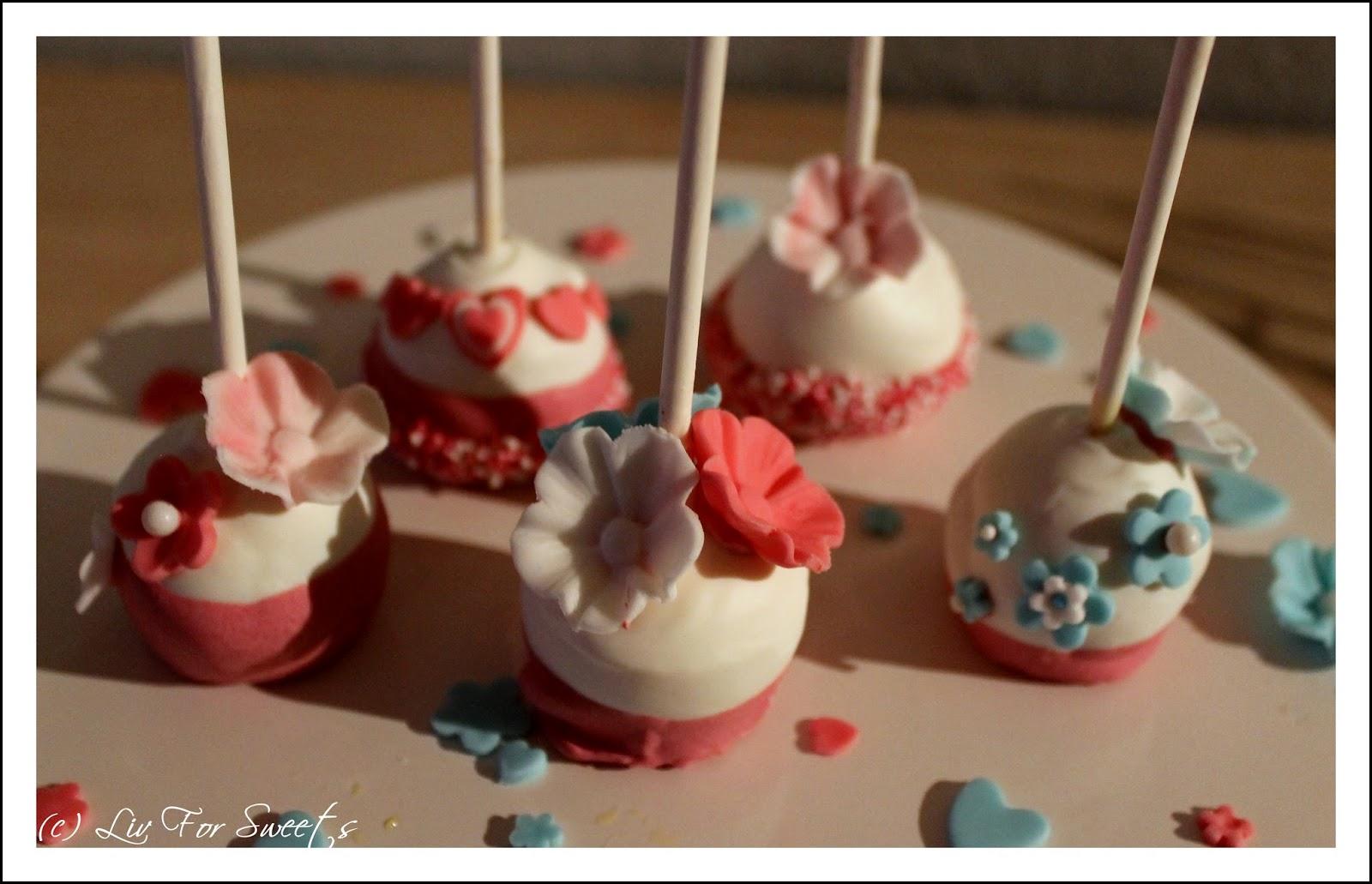 Cake-Pops mit einer Deko aus Fondantblumen und Zuckerperlen