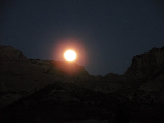 Moonrise over a desert canyon.