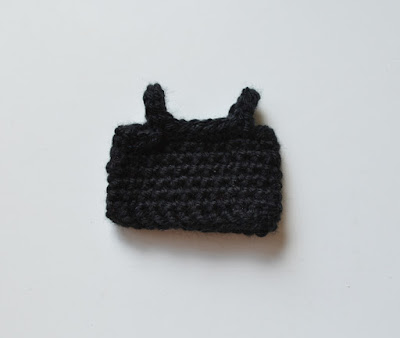 Close up and front view of black sleeveless top. A simple tube with crochet cord shoulder straps.