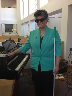 Laurel standing by grand piano