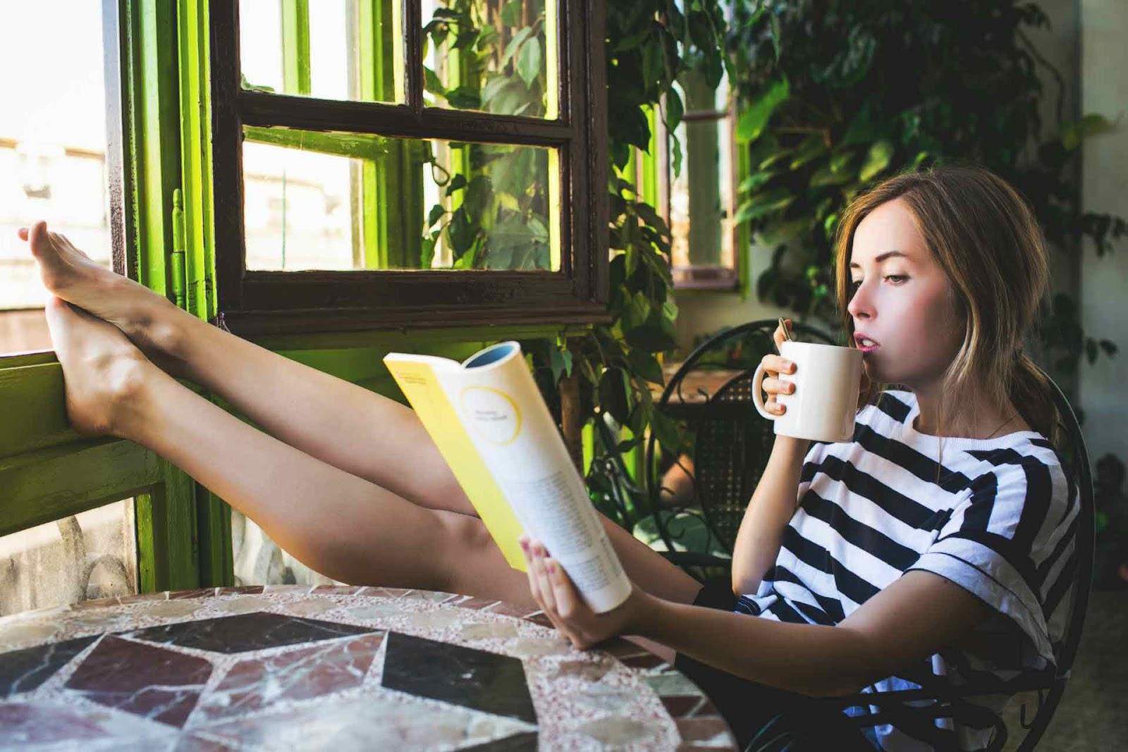 Beautiful girl drinking coffee while reading
