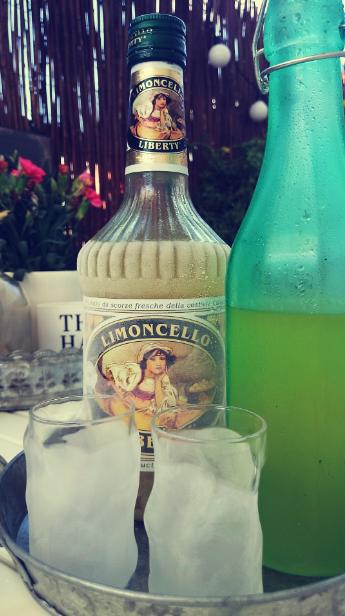 Butelka z korkiem Retro Treats, ocynkowane tace, mata wiklinowa na balkonie, kieliszki Bormioli Rocco