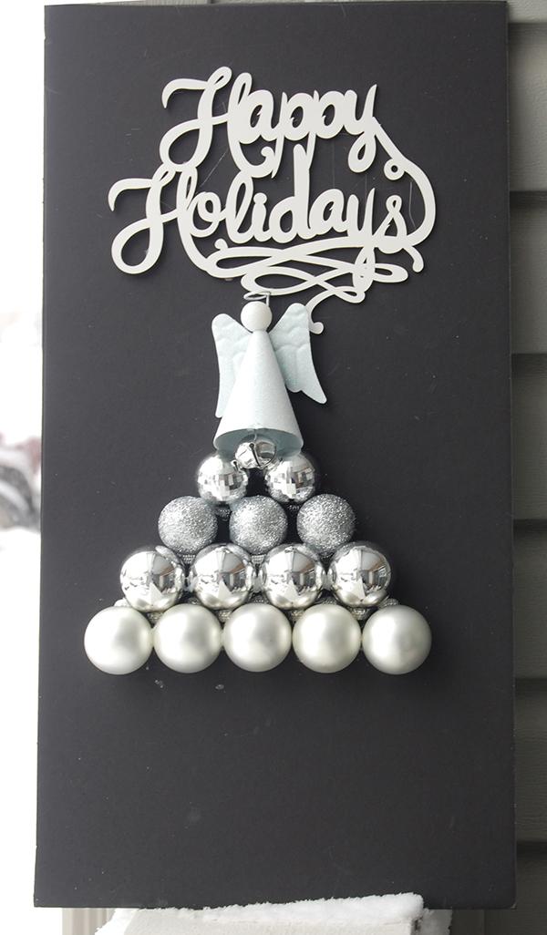 White Happy Holidays sign, white glitter ornament, silver ornament bulbls on black foam board