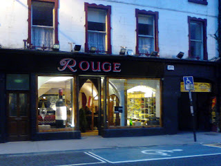 Twilight photo of Rouge Cafe, Galway - with a giant wine bottle in the front window