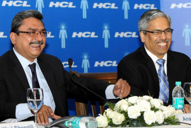 two men laughing at a table with HCL logo in the background