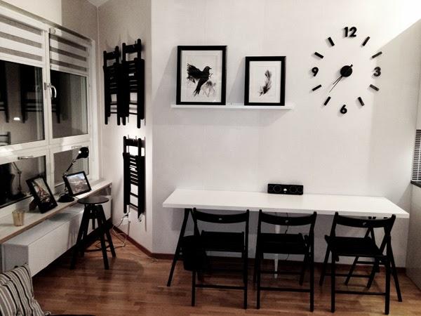 lägenhet i stockholm, svarta och vita prints, artprints fågel, svart fågel, svart och vitt kök, svart klocka, vita väggar, stolar på väggen, tavlor prints, tavlor i köket, tavellist, vit hylla i köket