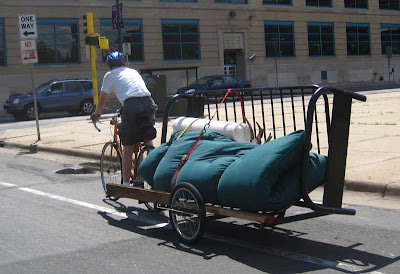 Bicyclist pulling a trailer with a futon sofa frame and futon attached
