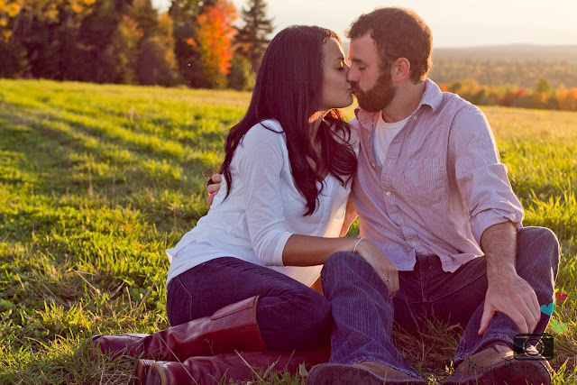 couple kissing while sitting in a field