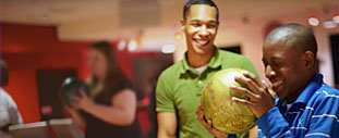 Two African American young men laugh as they bowl