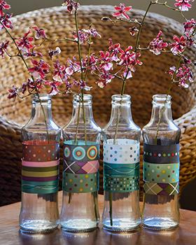 Garrafinhas de vidro + fitas coloridas = vasos para flores