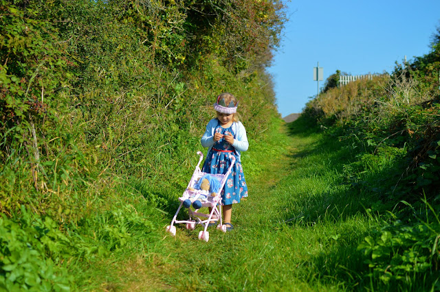 Girl pushes doll in pushchair