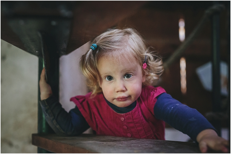 A toddler playing in a barn