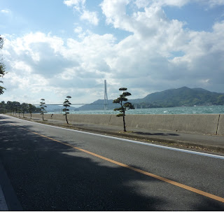 The Shimanami Kaido Bikeway along side the ocean on Ikuchijima with the Tatara Bridge in the distance