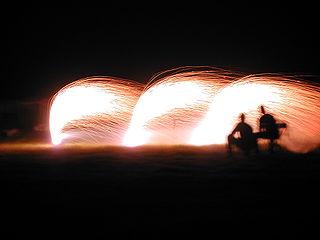 silueta de dos personas con fondo de juegos pirotécnicos sobre cielo nocturno oscuro