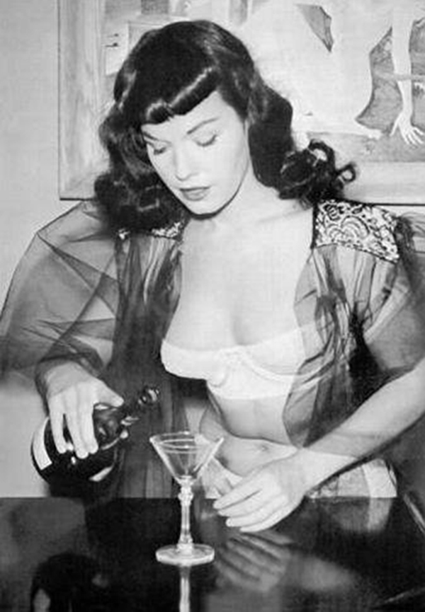 a candid photo of bettie page pouring champagne into a glass