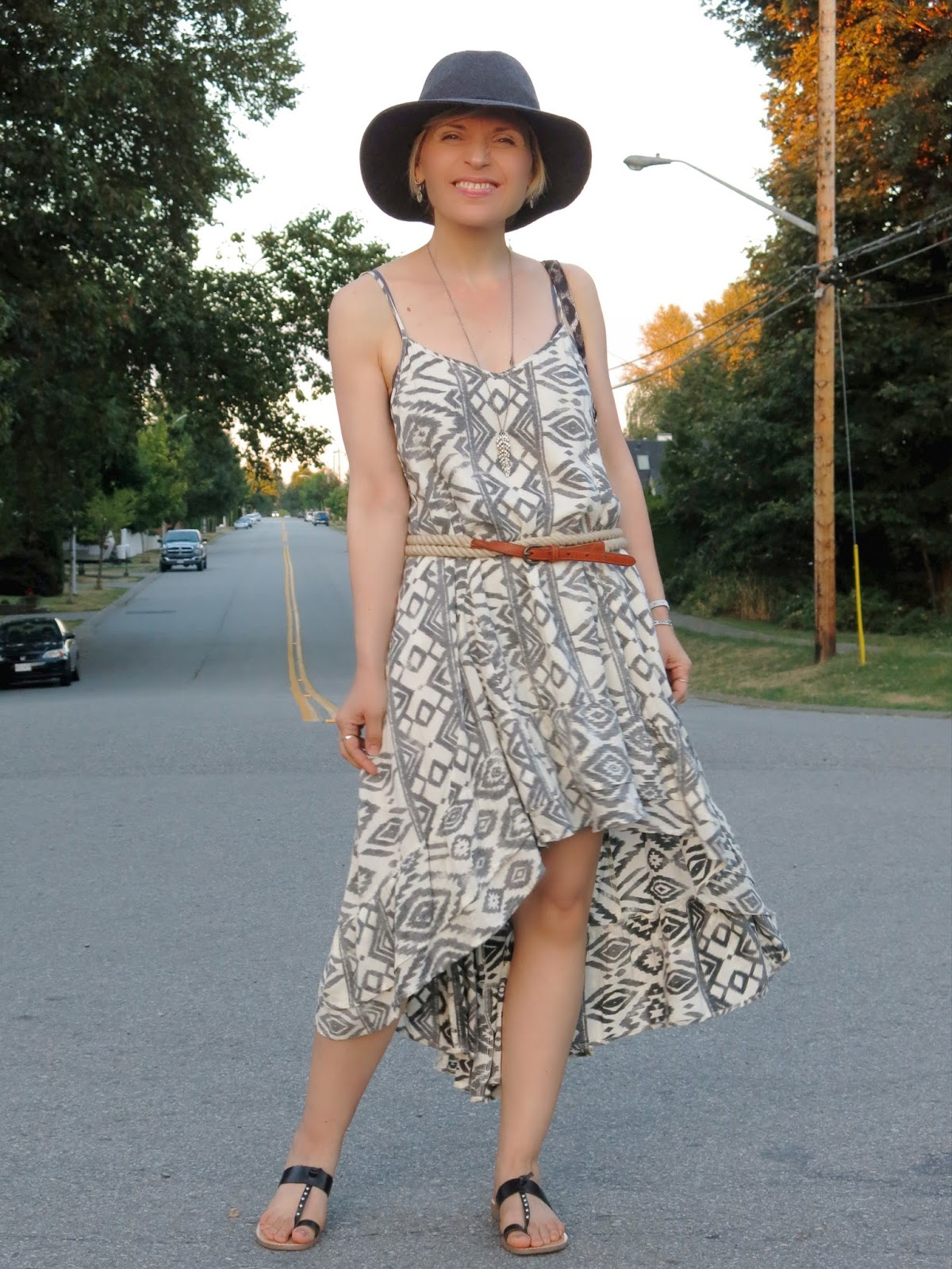 styling a high-low sundress with a double-wrap belt, floppy hat, and thong sandals
