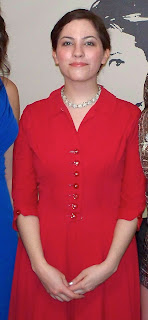 Colour photo of a young woman in a red dress.