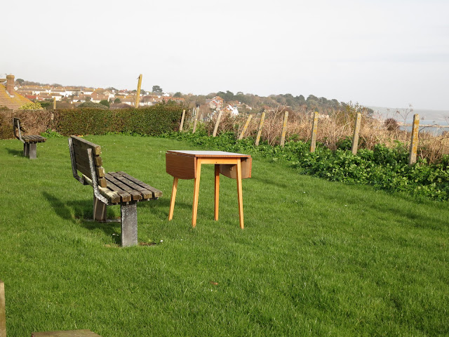 Kitchen table with drop-leaves out in the open, on grass, by public bench