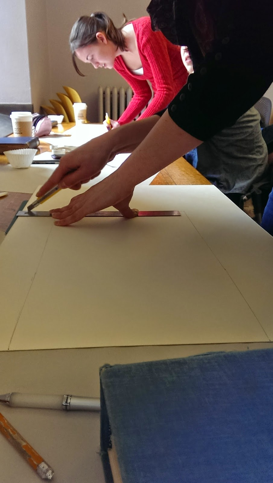 Two girls are measuring and cutting boards that are to be used for making a book shoe