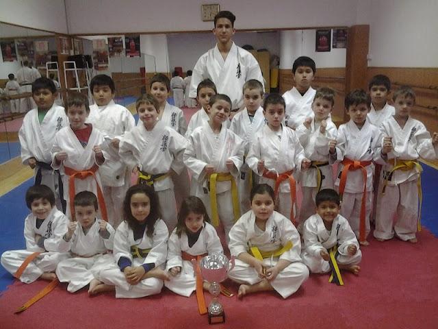 competidor de karate con grupo de pequeños karatekas