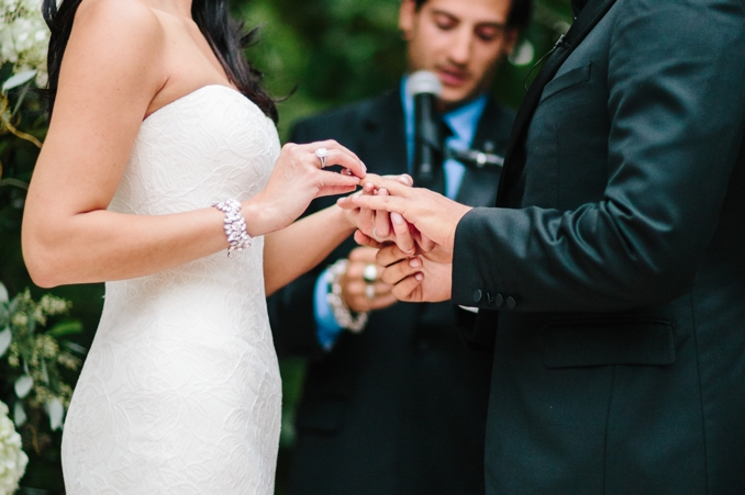 bride putting the ring on the grooms finger