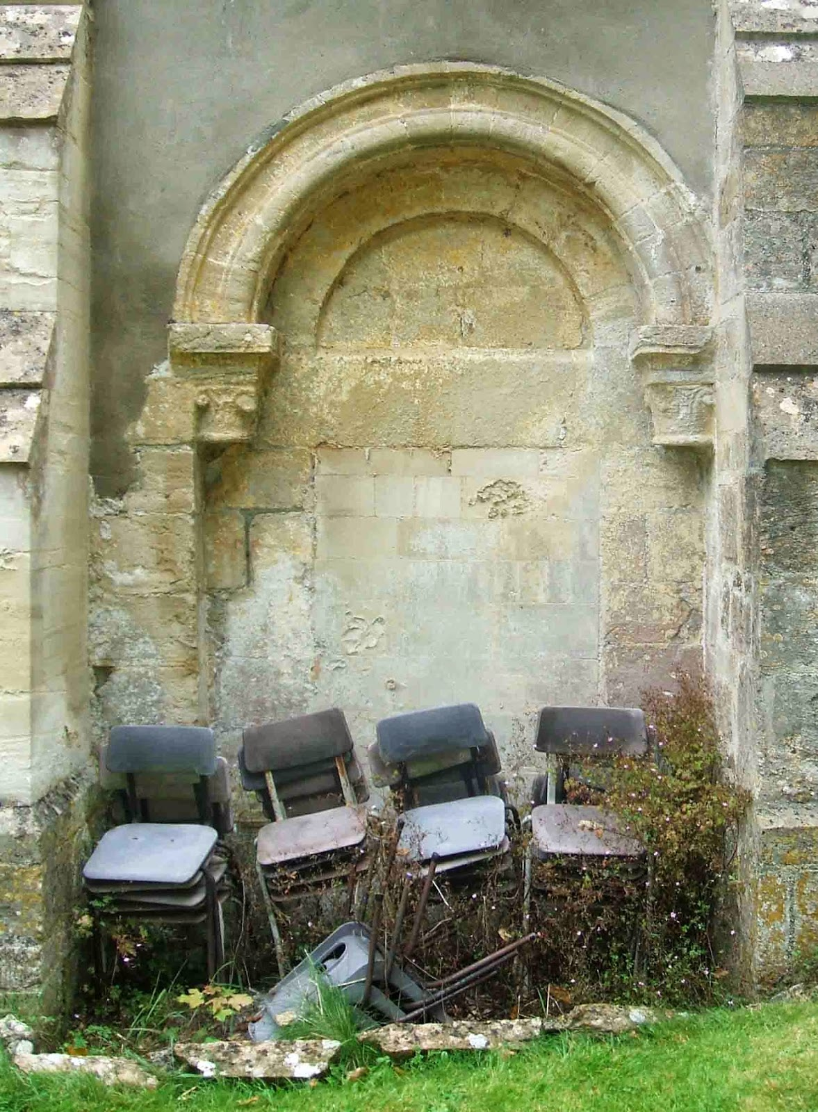 Chairs piled up outside the poor neglected Norman arch at Coulston, Wiltshire