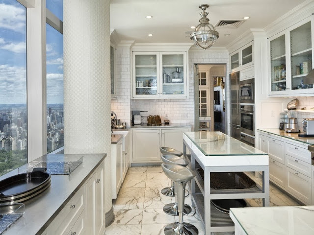 Kitchen in a NYC penthouse with marble floor, windows with a view of central park, subway tile backsplash, kitchen island with counter seating and glass upper cabinets