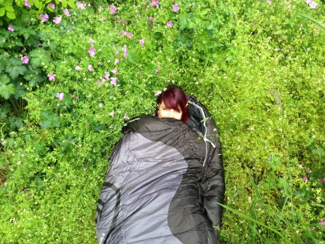 Jennifer Tulip in a sleeping bag in wildflower meadow