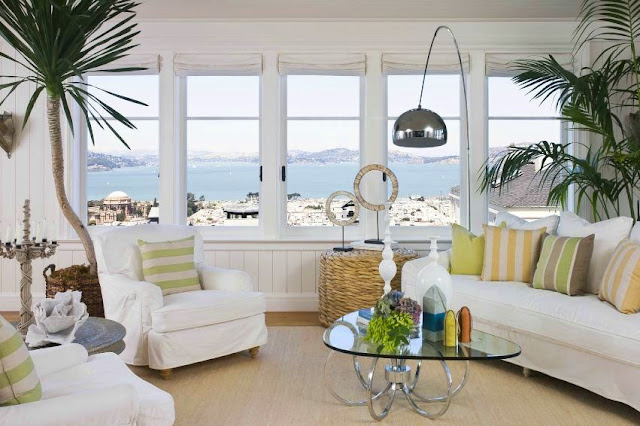 Family room in a san francisco mansion with white paneled walls, white sofa, two white armchairs with striped green and grey accent pillows, a glass coffee table, two palm trees, a modern metal reading lamp, and five windows with white rollup shades and an ocean view