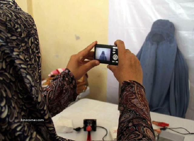 A burqa-clad Afghan woman has her picture taken