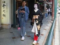 四条通りを西へ歩く真咲さんと男衆さん。