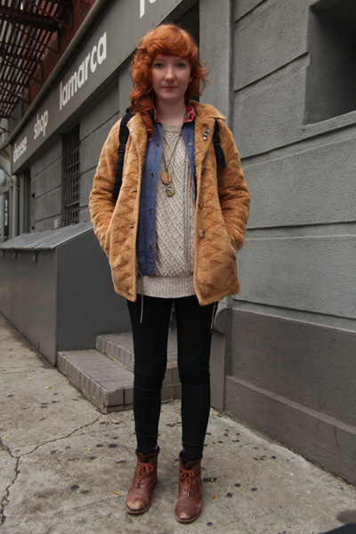 School of Visual Arts SVA in New York City student wears a faux fur tawny jacket over a blue denim shirt with plaid collar detailing, worn open over a chunky crew neck cream off white sweater and black leggings tucked into brown boots with red laces. All of this was accesorized with a silver fleur de lis lapel pin, a bronze leaf pendant, a silver stag necklace and a mountain print brown corduroy two tone backpack.