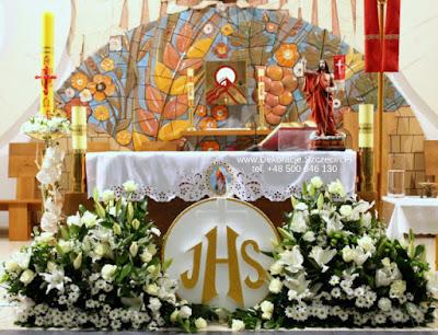 Dekoracja ołtarza na Pierwszą Komunię Świętą kwiaty i duża hostia