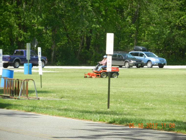 The BLV clerk's daughter mowing the BLV ballfield area,with the BLV ranger pickup to the left .
