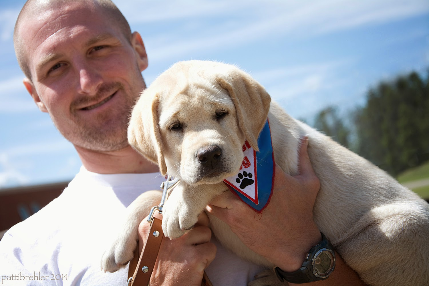 A bald man wearing a white t-shirt is smiling at the camera, he is holding a small yellow lab puppy in his left arm. The puppy is looking at the camera and is wearing a blue Future Leader Dog bandana.