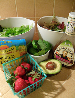 bowls of lettuce and basil, half avocado, half basket strawberries, sliced almonds, dressing
