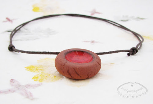 Ceramiczny naszyjnik uformowany z brązowej gliny z czerwonym oczkiem 2