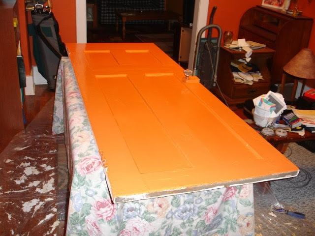 Orange bathroom door being painted on a table.